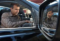 正在汽车里用笔记本测试WiMAX网络带宽的工程师