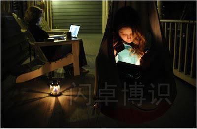 大卫·豪比用现场光拍摄的正在阳台上读书的女儿Emily
